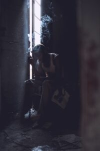 Man smoking a cigarette in sad appartment